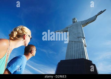 Couple at Christ the Redeemer statue (Cristo Redentor), Corcovado, Rio de Janeiro, Brazil, South America - Stock Photo