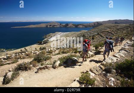 Backpackers hiking on Isla del Sol (Island of the Sun), Lake Titicaca, Bolivia, South America - Stock Photo
