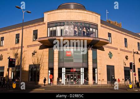 Modern Overgate shopping mall displaying company names and January Sale signs with discount prices on the windows - Stock Photo