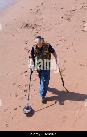 Man on beach using metal detector Teignmouth Devon England - Stock Photo