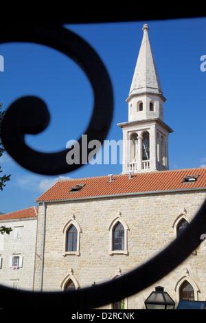 Church belltower viewed through wrought iron railings of the Old Town, Bidva, Montenegro, Europe - Stock Photo