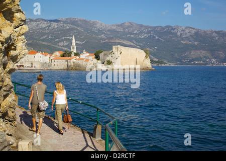 Couple walking along coast towards Old Town, Budva, Montenegro, Europe - Stock Photo
