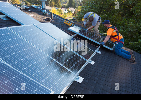 Caucasian men installing panels on roof - Stock Photo