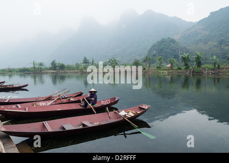 An unidentified woman sits in her «taxi»-boat while waiting for tourists on January 19, 2008 in the Red River Delta, - Stock Photo