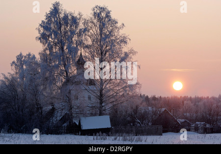 An orthodox church in Russian village in sunset in winter - Stock Photo
