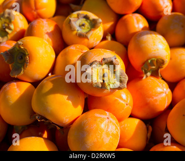 Persimmon ripe fruits pattern in market display - Stock Photo