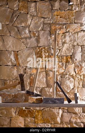 Hammer mason tools of stonecutter masonry work in a contruction stone wall - Stock Photo