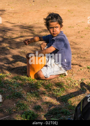 A young Hispanic Paraguayan boy sits on the dirt and plays with a ceramic block used in house construction. - Stock Photo
