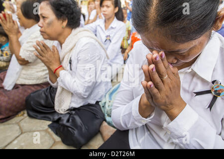 Phnom Penh, Cambodia. 1st February 2013.  A mourner prays as the King's funeral procession passes her in Phnom Penh. - Stock Photo