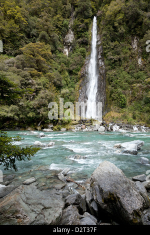 Thunder Creek Falls ends in the Haast River, New Zealand - Stock Photo