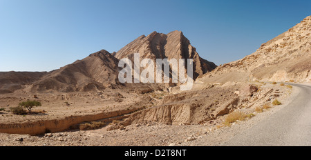 Scenic ridged brown rock at the road in stone desert - Stock Photo
