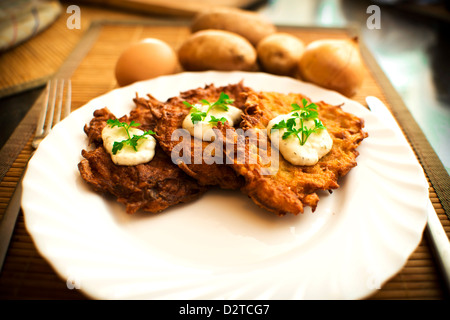 potato pancake with sour cream and parsley - Stock Photo