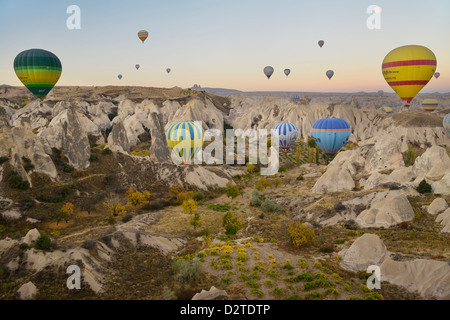 Many hot air balloons over the Red Valley with Uchisar in Cappadocia Goreme National Park Nevsehir Turkey at dawn - Stock Photo
