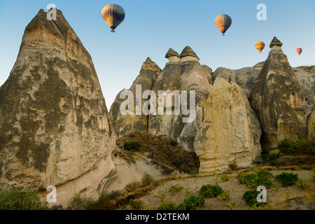 Cave homes in fairy chimneys of Cavusin Cappadocia Goreme National Park Nevsehir Turkey with hot air balloons - Stock Photo