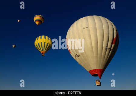 Hot air balloons against a blue sky with moon in Cappadocia Goreme National Park Nevsehir Turkey - Stock Photo