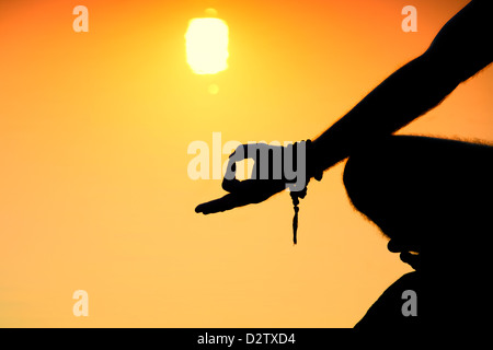 Sunrise silhouette of a mans hand whilst meditating on rocks at an Indian lake. Andhra Pradesh, India - Stock Photo