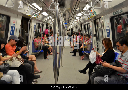 Travelers sitting inside a Singapore MRT subway train carriage and viewing their phones, etc. - Stock Photo