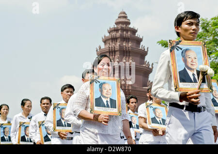 People holding photos of the  late king Norodom Sihanouk  march around Independence Monument  during his funeral - Stock Photo