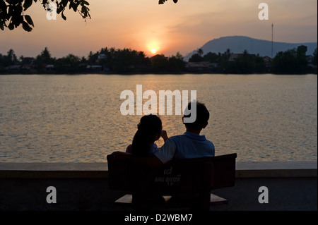 Kampot, Cambodia, a young couple watching the sunset - Stock Photo