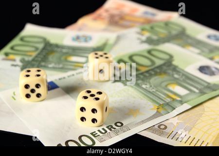 Three dice on Euro bills - Stock Photo