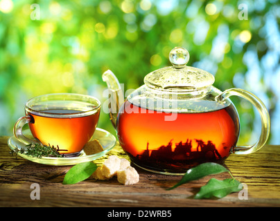 Cup of tea and teapot on a blurred background of nature. - Stock Photo