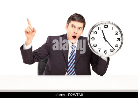 Angry businessman sitting and holding a wall clock isolated on white background - Stock Photo