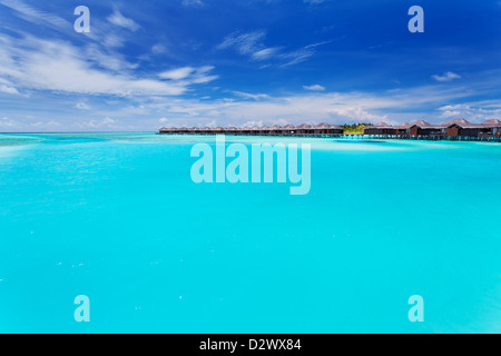 Overwater villas in tropical blue laggon of Maldives - Stock Photo