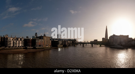 Panoramic river view East ward towards London Bridge from Millennium Bridge with early morning sun rising near the - Stock Photo