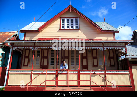 Woman from Vieux Fort. St Lucia standing on the porch of her traditional wooden house - Stock Photo