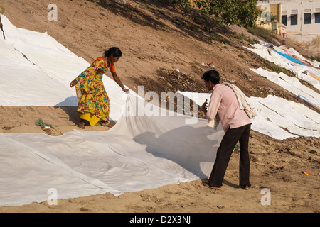 White sheets being laid out to dry on a ghat, Varanasi, India - Stock Photo