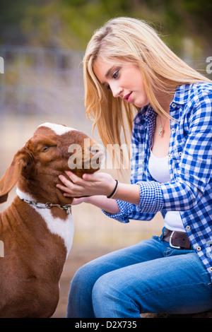 Female teenager petting goat - Stock Photo