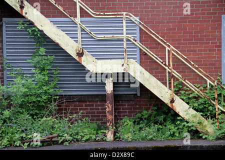 Rusty fire escape on side of a red brick building - Stock Photo