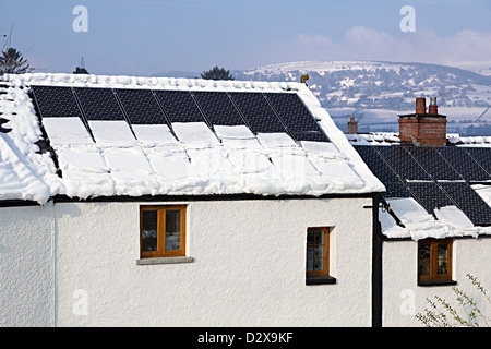 Snow sliding off solar pv panels and putting weight onto gutters of house, Llanfoist, Wales, UK - Stock Photo