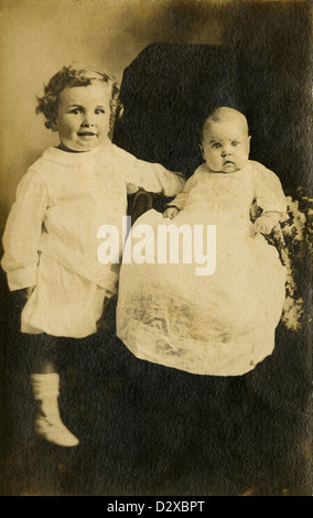 Circa 1910s photograph, toddler and his baby brother or sister in Edwardian dress. - Stock Photo