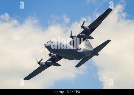 A C130 military plane banks in the sky - Stock Photo