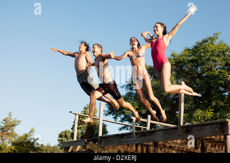 Friends jumping off dock - Stock Photo