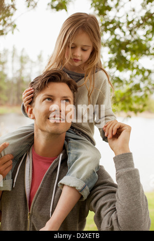 Father carrying daughter on shoulders at lakeside - Stock Photo