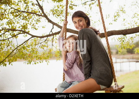 Portrait of mother and daughter on swing at lakeside - Stock Photo
