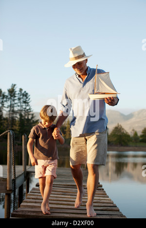 Grandfather and grandson with toy sailboat walking along dock over lake - Stock Photo
