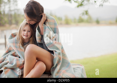 Portrait of smiling daughter wrapped in blanket with mother at lakeside - Stock Photo