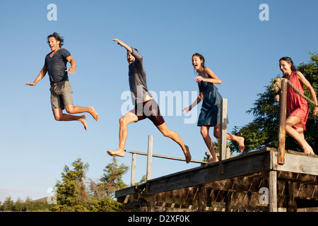 Enthusiastic friends jumping off dock - Stock Photo