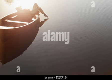 Woman laying in boat on sunny lake - Stock Photo