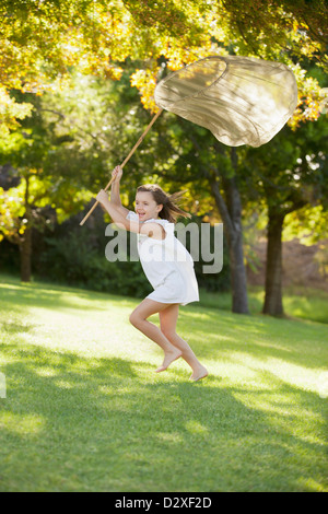 Happy girl running with butterfly net in grass - Stock Photo