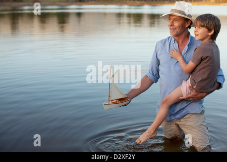 Grandfather and grandson with toy sailboat in lake - Stock Photo