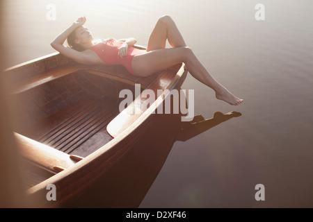 Serene woman sunbathing in boat on lake - Stock Photo