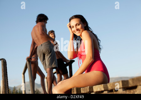 Portrait of smiling woman in bathing suit on dock - Stock Photo