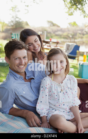 Portrait of smiling family picnicking at lakeside - Stock Photo