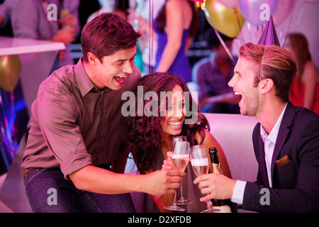 Enthusiastic friends toasting champagne flutes in nightclub - Stock Photo