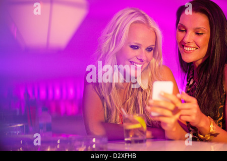 Smiling women looking down at cell phone in nightclub - Stock Photo
