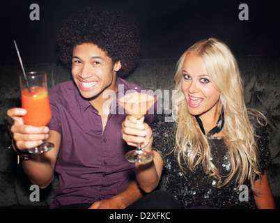 Portrait of enthusiastic couple toasting cocktails in nightclub - Stock Photo